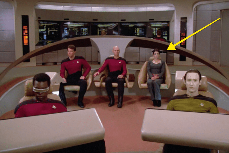The crew are all sat in the bridge in their seats, with a yellow arrow pointing at Deanna Troi